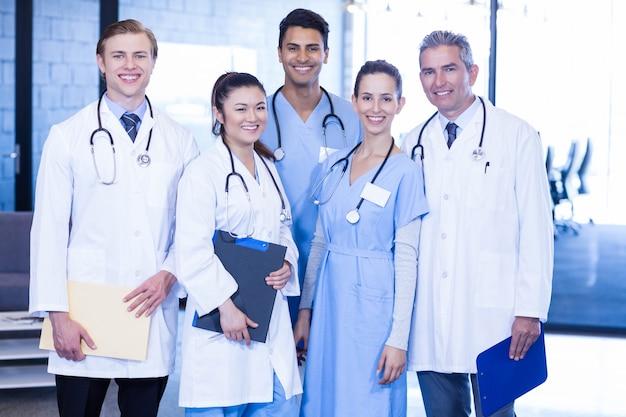 Portret zespołu medycznego stojąc razem i uśmiechając się w szpitalu