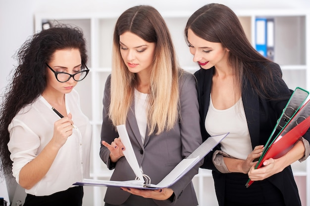 Portret zespołu szczęśliwych przedsiębiorców stojących na korytarzu urzędu, patrząc na kamery, uśmiechając się.