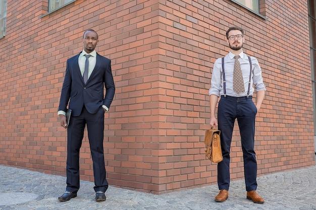 Portret zespołu wieloetnicznego biznesu. dwóch mężczyzn stojących na tle miasta. jeden mężczyzna jest afroamerykaninem, drugi europejczykiem. koncepcja sukcesu w biznesie