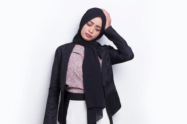 Portret zestresowanej chorej azjatyckiej muzułmańskiej kobiety biznesu z bólem głowy na białym tle