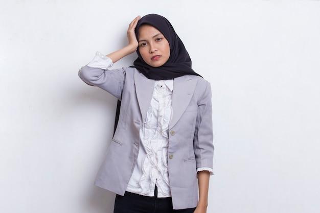 Portret zestresowanej chorej azjatyckiej muzułmańskiej kobiety z bólem głowy na białym tle