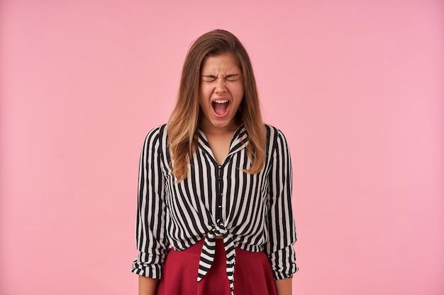 Portret zestresowanej młodej brunetki, trzymając oczy zamknięte, krzycząc z szeroko otwartymi ustami, stojąc na różowo z opuszczonymi rękami