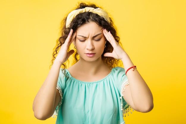 Portret zestresowanej, skoncentrowanej dziewczyny z bólem głowy, zamkniętymi oczami. emocjonalna dama w bólu masuje skronie.