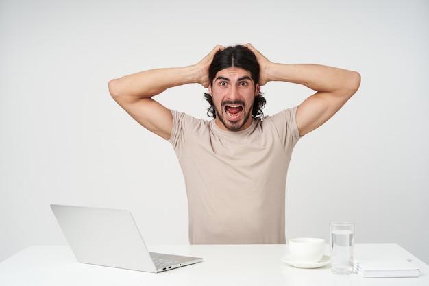 Portret zestresowany biznesmen z czarnymi włosami i brodą. koncepcja biura. trzyma głowę i krzyczy z walki. siedząc w miejscu pracy i na białym tle nad białą ścianą