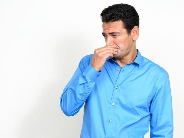 Portret zestresowany dojrzały biznesmen patrząc zniesmaczony i zakrywający nos