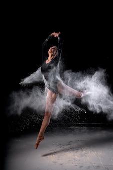 Portret zgrabnej smukłej tancerki baletowej skaczącej, ubranej w body, zmysłowo poruszającej się wśród latającej mąki, która pokrywa jej ciało, na czarnym tle studia. balet, spektakl