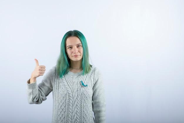 Portret zielone włosy dziewczyna pozuje do kamery i daje kciuki do góry.