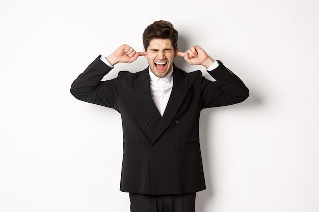 Portret zirytowanego i zaniepokojonego biznesmena w czarnym garniturze, z zamkniętymi uszami i wrzeszczącego, narzekającego na głośny hałas, stojącego na białym tle.