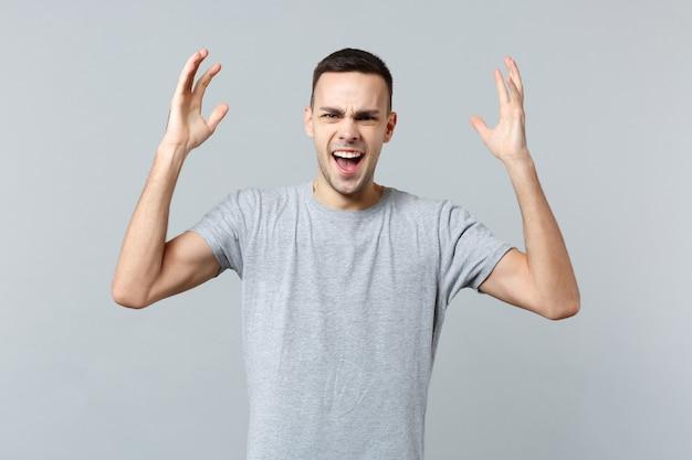 Portret zirytowanego krzyczącego młodego mężczyzny w zwykłych ubraniach wznoszących się, rozkładających ręce