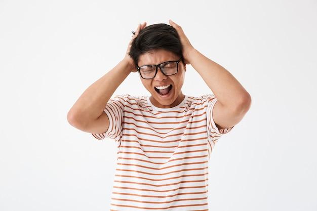 Portret zirytowanego młodego człowieka azji w okularach przeciwsłonecznych
