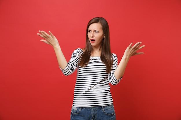Portret zirytowanej, zaniepokojonej młodej kobiety w niezobowiązującym ubraniu w paski, stojącej i rozkładającej ręce
