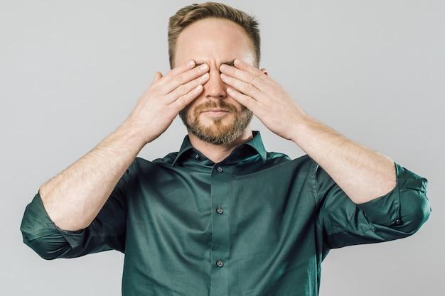 Portret zirytowany młody człowiek obejmujących oczy rękami