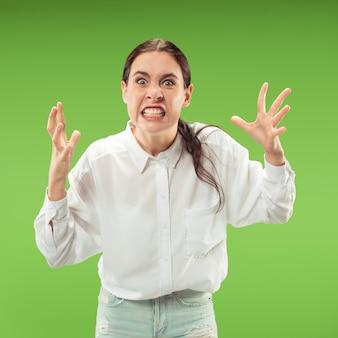 Portret złej kobiety na białym tle na zielonej ścianie