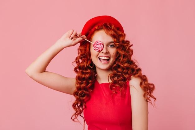 Portret złośliwej dziewczyny z falistymi rudymi włosami w jasnej górze i berecie zakrywającym oko lizakiem.