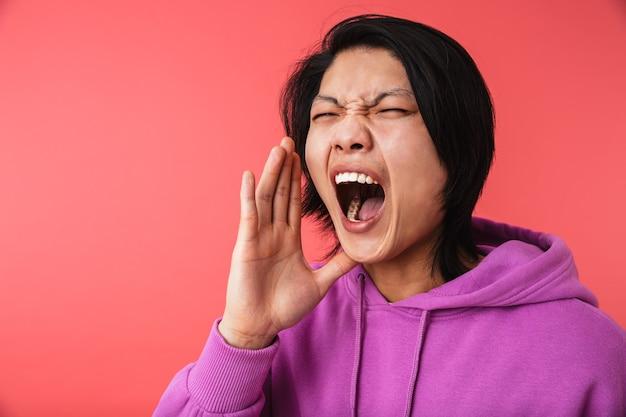 Portret zły azjatycki facet ubrany w bluzę krzyczy, będąc wściekły na białym tle nad czerwoną ścianą