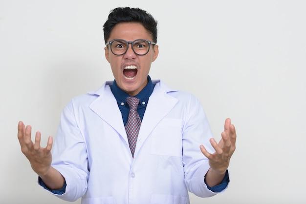 Portret zły azjatycki lekarz mężczyzna z okularami krzyczy i krzyczy