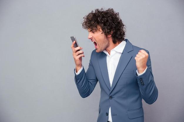 Portret zły biznesmen krzycząc na smartfonie na szarej ścianie