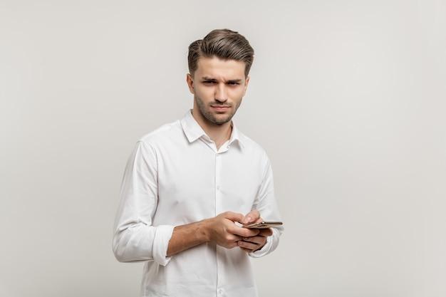 Portret zły facet ubrany w białą koszulę trzymającą telefon komórkowy na białym tle