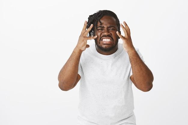 Portret zły facet z warkoczykami, pozowanie na białej ścianie