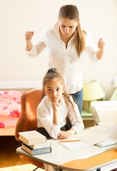 Portret zły matka przysięga na córkę odrabiającą pracę domową