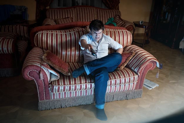 Portret zły mężczyzna przełączający kanał telewizyjny siedząc na kanapie