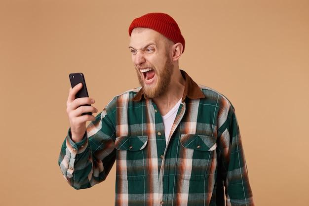 Portret zły młody człowiek krzyczy na swój telefon komórkowy