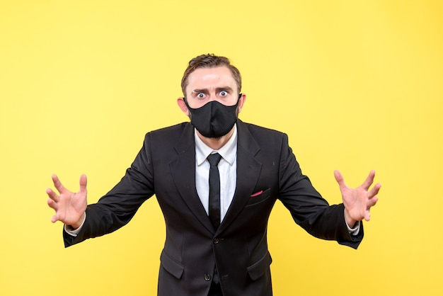 Portret zły młody człowiek w masce medycznej na żółto