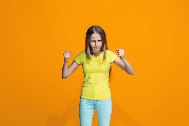 Portret zły teen dziewczyna na pomarańczowej ścianie