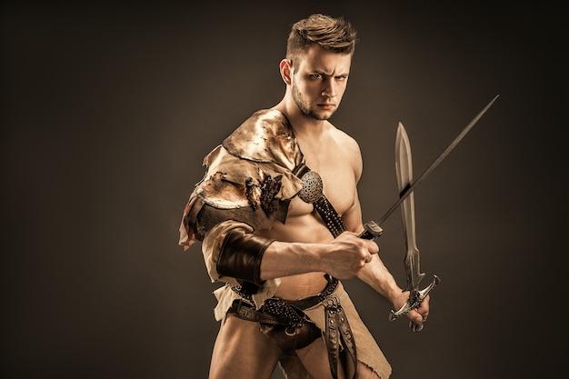 Portret zły wojownik w skórzane ubrania z mieczami