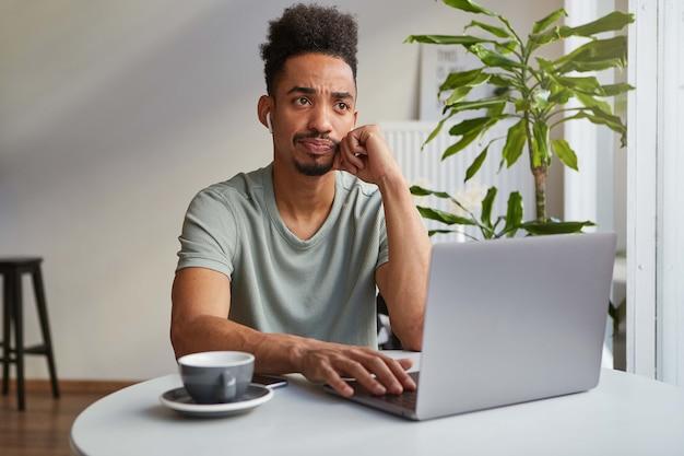 Portret zmarszczonego, atrakcyjnego, myślącego chłopca afroamerykanów, siedzi w kawiarni, pracuje przy laptopie, dotyka policzka i ze smutkiem patrzy w górę, myśli o terminie.