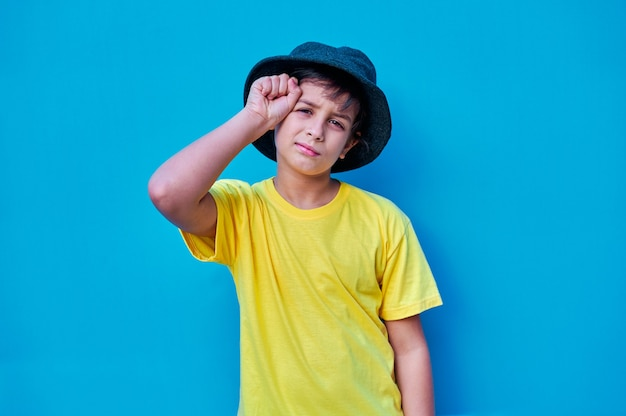 Portret zmartwionego chłopca w żółtej koszulce i kapeluszu