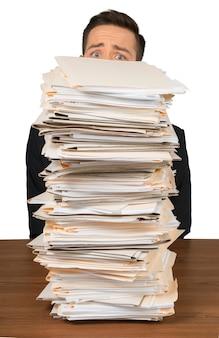 Portret zmartwionego pracownika za stosem dokumentów