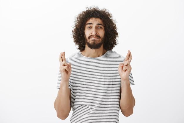 Portret zmartwionego przystojnego latynosa z fryzurą afro w t-shircie w paski, niespokojnym gryzieniem wargi i krzyżowaniem palców w nadziei lub modlitwie, marzenie marzenie się spełni