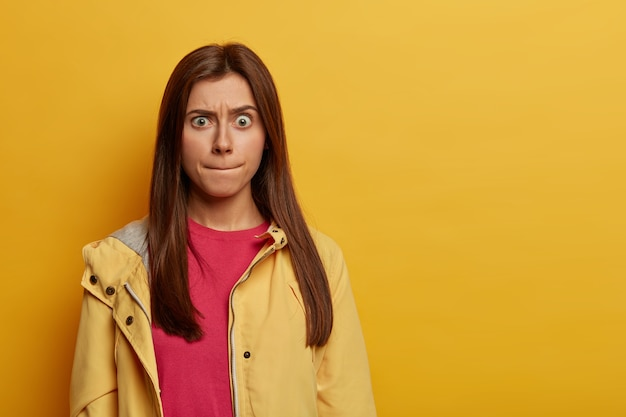 Portret zmartwionej emocjonalnie europejki zaciska usta, próbuje kontrolować swoje emocje, unosi brwi, nosi różowy sweter i anorak