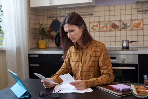 Portret zmartwionej młodej kobiety siedzącej w kuchni, patrząc na rachunki i zastanawiającej się, jak spłacić wszystkie długi za czynsz i studia. pojęcie problemów finansowych.