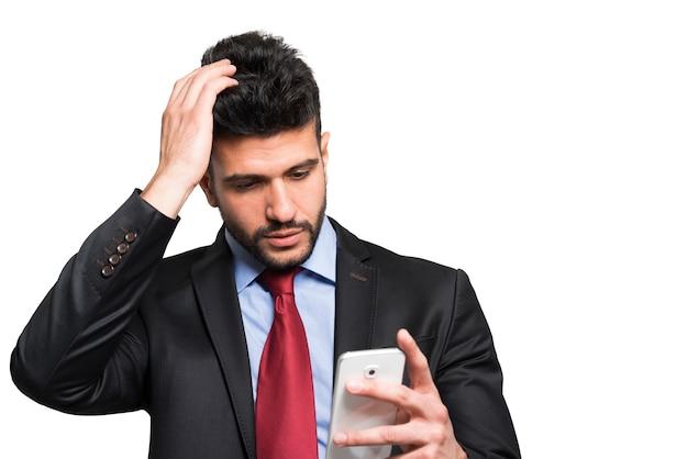 Portret zmartwiony mężczyzna patrzeje jego smartphone