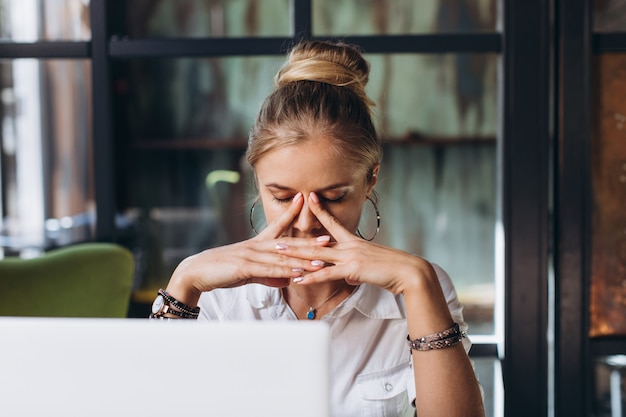 Portret zmęczona blond biznesowa kobieta z laptopem
