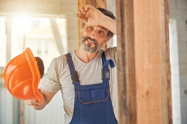 Portret zmęczonego, brodatego, dojrzałego robotnika ocierającego pot z czoła