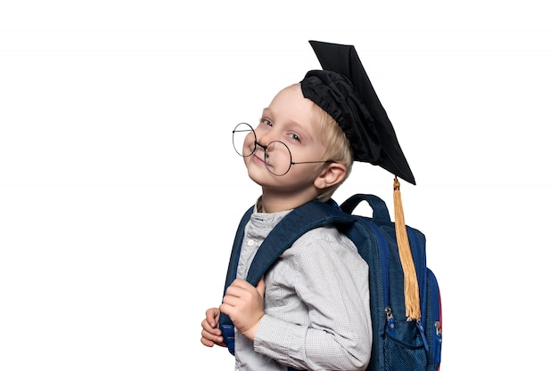 Portret zmęczonego chłopca w okularach, akademickiego kapelusza i tornistra. koncepcja szkoły. izolować