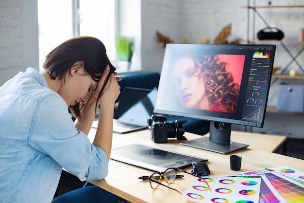 Portret zmęczonego grafika pracuje w godzinach nadliczbowych w biurze. zestresowany pracownik ma objawy zmęczenia oczu. miejsce pracy retuszera w studiu fotograficznym. koncepcja wypalenia i przepracowania. agencja kreatywna.