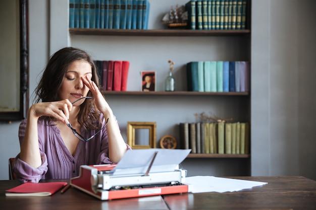 Portret zmęczonego kobiety dziennikarza obsiadanie przy stołem
