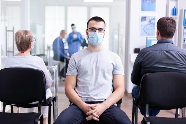Portret zmęczonego młodego mężczyzny z maską przeciw koronawirusowi w szpitalnej poczekalni, patrząc na kamerę