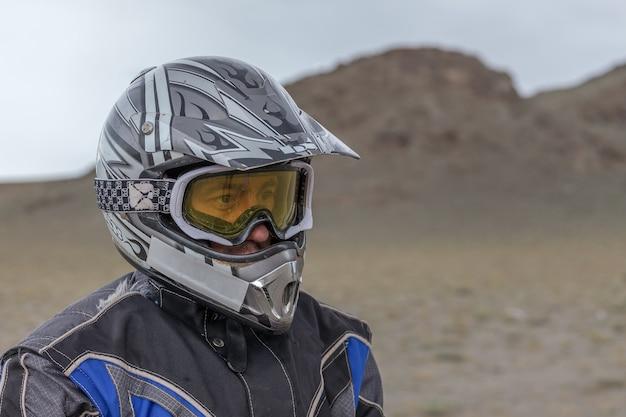 Portret zmęczonego motocyklisty na tle gór ałtaj