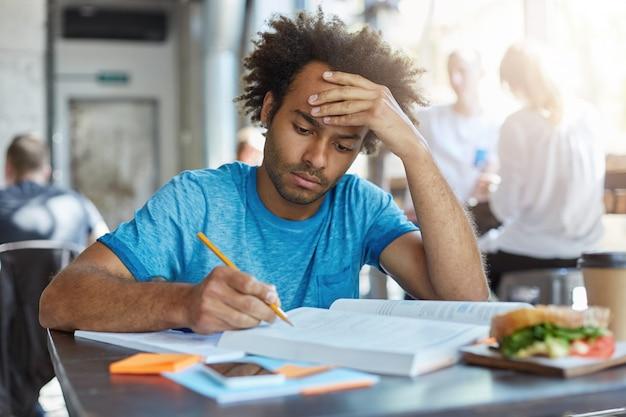 Portret zmęczonego, poważnego mężczyzny rasy mieszanej, ubranego niedbale, siedzącego przy drewnianym biurku w kawiarni, piszącego notatki i czytającego książki po obiedzie, jedzącego hamburgera, trzymając rękę na głowie próbując się skoncentrować