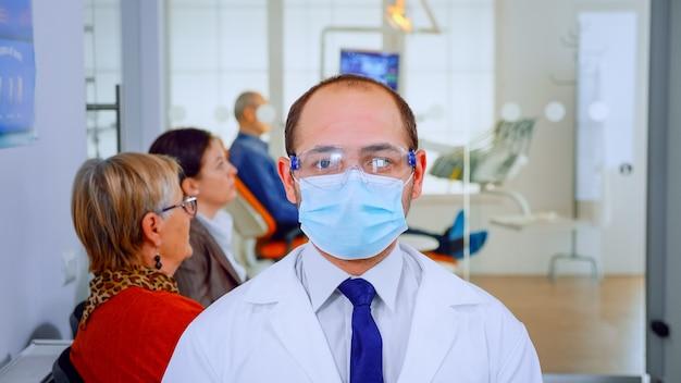 Portret zmęczonego stomatologa noszenia maski ochronnej w aparacie w gabinecie stomatologicznym, podczas gdy pacjenci czekają go w tle. dentysta patrząc na kamerę internetową siedząc na krześle w klinice stomatologicznej.