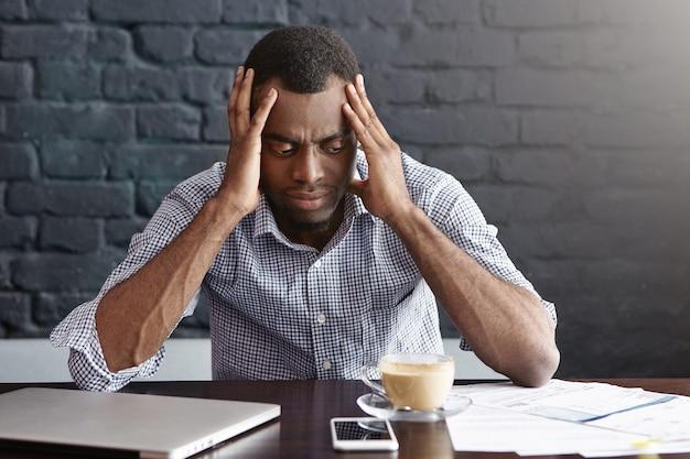Portret zmęczonego, wyczerpanego, młodego ciemnoskórego pracownika dotykającego głowy