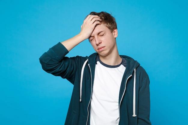 Portret zmęczonego, wyczerpanego młodego człowieka w ubraniu, trzymając zamknięte oczy, kładąc rękę na głowie na białym tle na niebieskiej ścianie. ludzie szczere emocje, koncepcja stylu życia.
