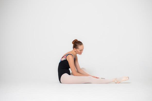 Portret zmęczonej baleriny na białym tle z bliska, młoda kobieta siedzi na podłodze.