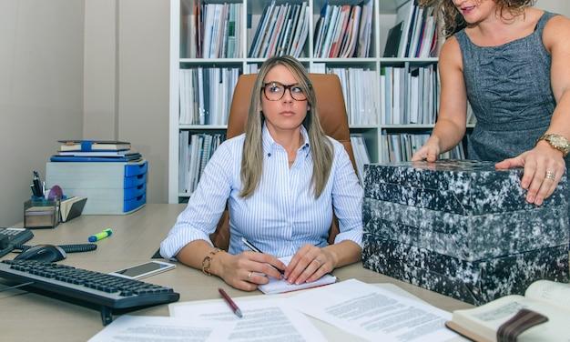 Portret zmęczonej blond sekretarki odbierającej foldery stos do pracy