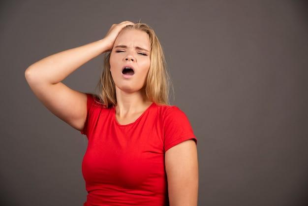 Portret zmęczonej kobiety dotyka jej głowy nad zmrokiem.